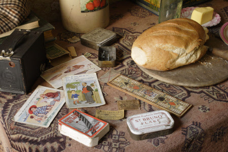 A loaf of bread, some butter, a tin of tobacco and other items on a side table in the parlour of the 1930s house in the Birmingham Back to Backs